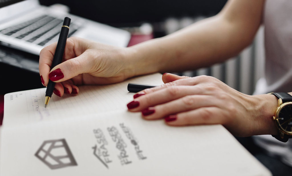 Fraser-logo_Woman-writing-on-notebook